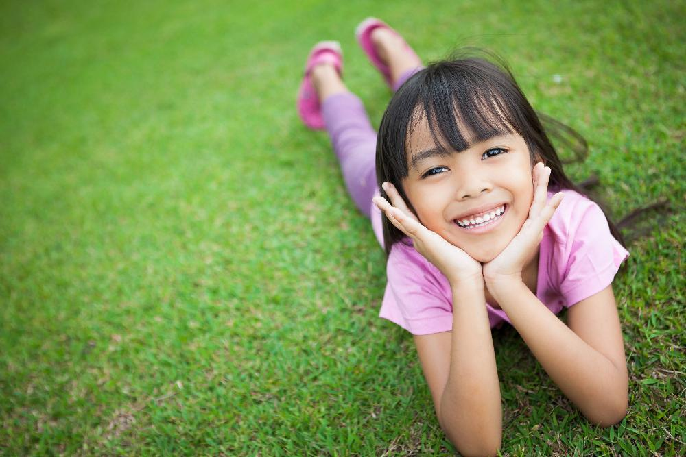 Young girl smiling in the grass | Children's Dentist Edmond OK