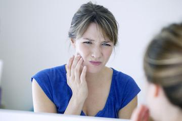 Woman holding side of her face with bad tooth pain | Root Canals in Edmond OK